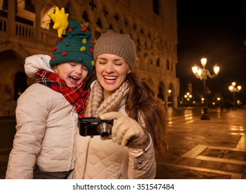 Holiday family trip to Venice, Italy can change the whole Christmas experience. Happy mother and child in funny Christmas hat looking on photos in digital camera on Piazza San Marco in the evening
