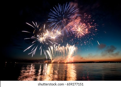 Holiday fireworks above water with reflection on the black sky background