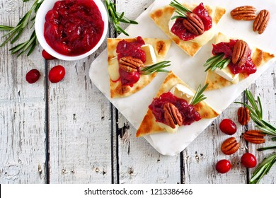 Holiday flatbread appetizers with cranberries, pecans and brie cheese. Above view table scene on a white platter.
