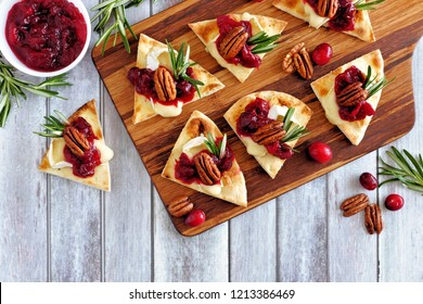 Holiday flatbread appetizers with cranberries, pecans and brie cheese. Top view table scene on a wooden platter.
