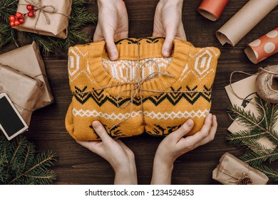 Holiday flatlay arrangement with woman's hands giving knitted sweater as present to man on dark wooden background