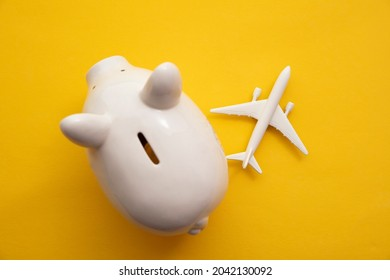 Holiday flight fare saving concept. Piggy bank with a toy plane. Vacation budget planning