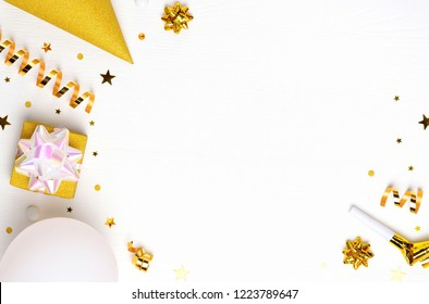 Holiday frame or background with balloon, gift, confetti, golden star, carnival cap and streamer. Flat lay style. Birthday or party greeting card with copy space.