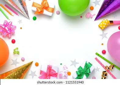Holiday frame or background with colorful balloon, gift, confetti, silver star, carnival cap and streamer. Flat lay style. Birthday or party greeting card with copy space.