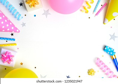 Holiday frame or background with colorful balloon, gift, confetti, silver star, carnival cap and streamer. Birthday or party greeting card. Flat lay, top view, copy space.