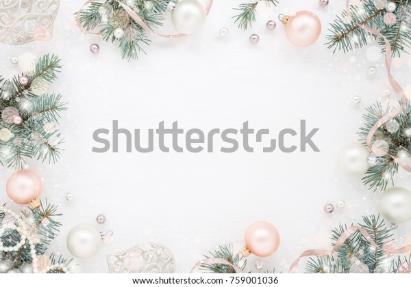 Holiday frame of Christmas decorations on white background with fir branch, pink balls, ribbon and pearls. Elegant New Year`s snowy card. Top view.