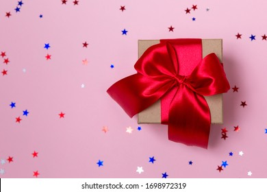 Holiday gift box with a big red bow on a pink holiday background with multicolored stars. Celebrity design.