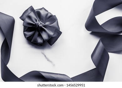 Holiday gift, decoration and sale promotion concept - Black silk ribbon and bow on marble background, flatlay