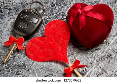 Holiday gift jewels in a box in the form of a heart with a bow and a car key with a red bow on a gray background. Valentine's Day.