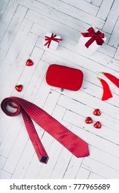 Holiday gifts for Valentine's day. Red tie, candy-hearts, jewelry and gift boxes on a white background.
