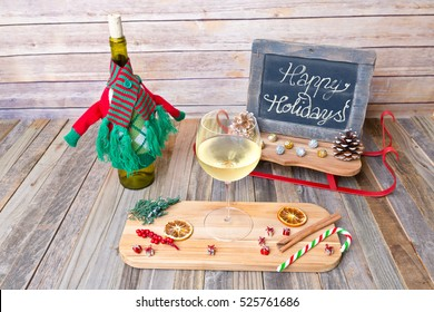 Holiday glass of white wine with chalkboard sign and decorations
