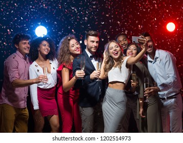 Holiday group selfie. Young friends having fun at New Year's Eve party and taking photo, copy space
