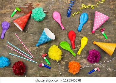 Holiday hats, whistles, balloons on old wooden background. Concept of children's birthday party. Top view.