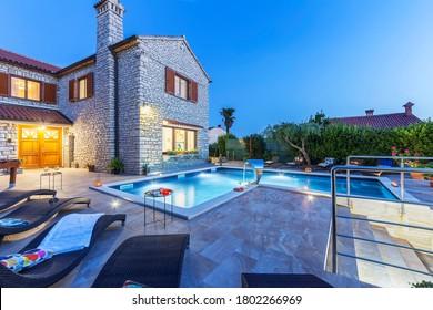 Ferienhaus mit Schwimmbad am Abend