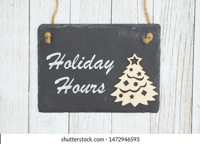 Holiday hours sign on retro chalkboard with Christmas tree on weathered whitewashed textured wood