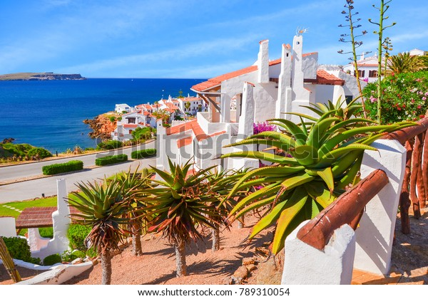 Holiday houses with green gardens on sea coast near Fornells village, Minorca island, Spain
