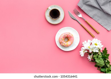 holiday lunch for woman with cup of americano, donut and flowers on pink background top view mock up
