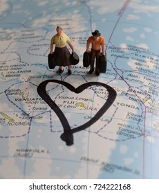 Holiday makers with luggage in miniature figures on map of Fiji islands