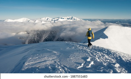 Holiday man with in winter snow landscape. Beautiful mountains view during sunset. Sunny frozen day. Healthy lifestyle and great for mental health. Mountains and trek.Lifetime experience on the hike,