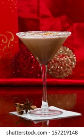 holiday martini with a sugar rim and lime and orange zest on top served on a table with decorations