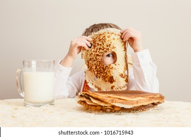 the holiday of Maslenitsa. The child took a bite of pancake. The child looks through the hole in the damn. Big baked pancake . food