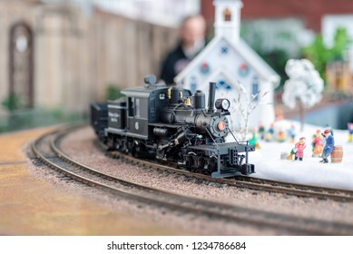 Holiday model train display with steam engine and church with miniature figures