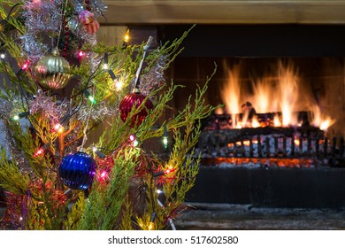 Holiday ornament hanging on tree with glowing fireplace in background