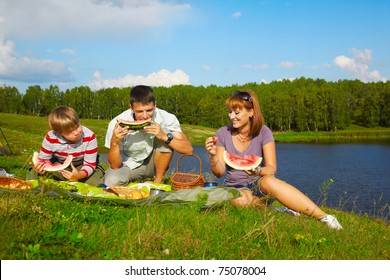 holiday outdoor portrait of happy families eating watermelon at the picnic near camp tent