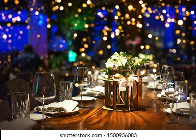 Holiday party blurred background made from decorated table with bouquet of flowers and colorful lights bokeh. Selective focus. Christmas dinner, festive table setting with flower decorations.