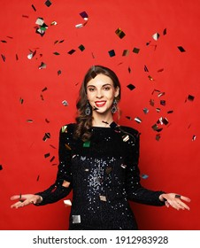 Holiday and party concept: beautiful young woman wearing evening dress standing under confetti rain over red background. Happy time.