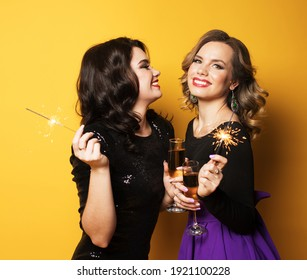 Holiday and party concept: Portrait of two young fashionable women with a champagne glasses and sparklers over yellow background