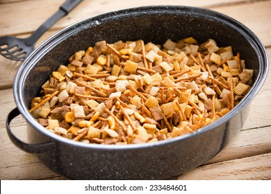 Holiday Party Food Mix - This is a shot of a party mix containing cereal, peanuts and pretzels in a roaster pan on an old wooden table.