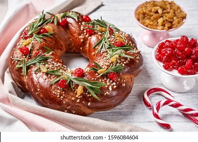 Holiday pastry: braided wreath decorated with dried cherries, white sultanas, rosemary on top on a white wooden background, sugar cane, dessert cutlery, close-up, horizontal