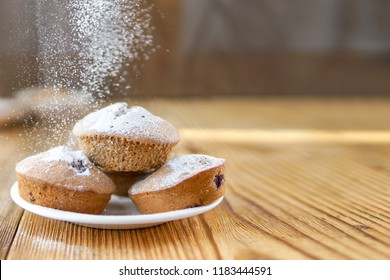 Holiday pastry muffins with falling suger powder near window light, sunshine