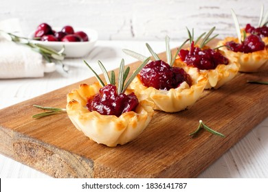 Holiday phyllo pastry appetizers with cranberries and baked brie. Serving board closeup against a white wood background.