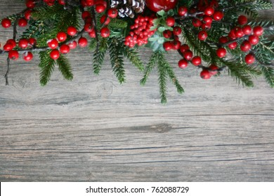 Holiday Pine Tree Branches and Berries Over Rustic Wood Horizontal Background