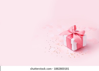 Holiday pink background with gift, white satin bow, ribbon. Valentine's Day, Happy Women's Day, Mother's Day, Birthday, Wedding, Christmas. space for text, banner, flyer - Shutterstock ID 1882800181