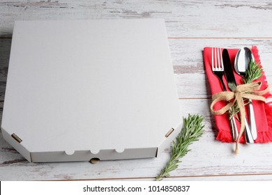 Holiday pizza delivery concept. Pizza box and cutlery on wooden table. Top view background.