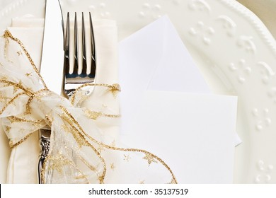 Holiday place setting with napkin, fork and knife tied with a gold ribbon. Blank card included.