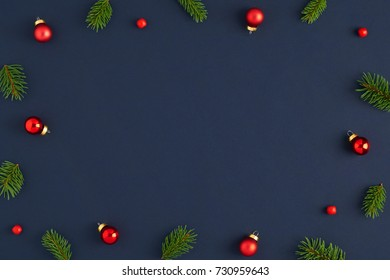 Holiday postcard. Xmas frame branches decorations in the red balls and red beads on a dark blue background. Ready Christmas background for your text