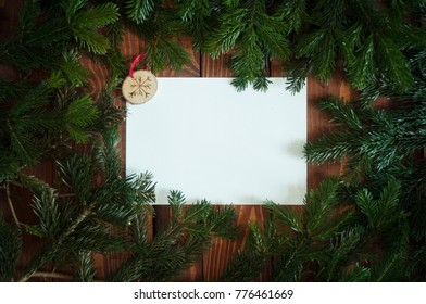 Holiday postcard. Xmas frame branches decorations on a dark wooden background. Ready Christmas background for your text. Copy space on a white paper in the middle.