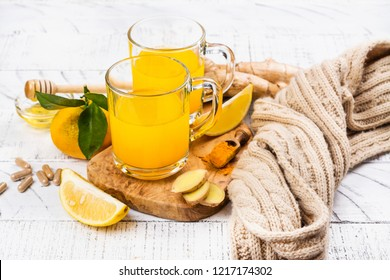 Holiday pre-detox turmeric, ginger and lemon drink in glass mugs. Beverage rich of vitamins for autumn and winter chilli days. Copy space