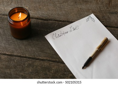 Holiday Scene With Blank Christmas List And Pen On Old Hardwood Table With All Natural Soy Candle In Brown Glass Jar Lit And Glowing Indoors On A Chilly Day