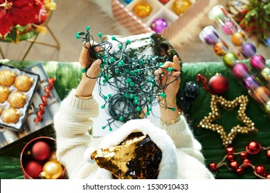 Holiday season. Upper view of elegant woman in sparkle gold sequin santa hat sitting on sofa in the modern living room at Christmas trying to untangle tangled christmas lights.