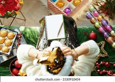 Holiday season. Upper view of stressed stylish housewife in sparkle gold sequin santa hat sitting on sofa in the modern living room at Christmas tired of the holiday bustle.