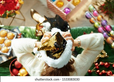 Holiday season. Upper view of stressed modern housewife in sparkle gold sequin santa hat sitting on sofa in the modern living room at Christmas.