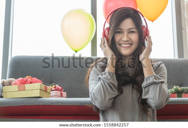 Holiday Seasonal and Happy Concept. Portrait of beautiful young asian woman with headphone smiling and enjoy with music in the living room with sofa, party balloon and gift boxes.