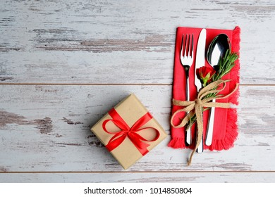 Holiday serving table with cutlery and gift on wooden table. Top view creative background with copy space for restaurant. Valentine's Day or woman day template.