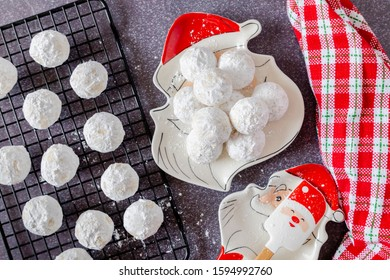 Holiday snowball cookies on Santa plate with Santa spoon holder and red and white plaid napkin
