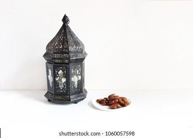 Holiday still life composition. Plate with date fruits and ornamental dark Moroccan, Arabic lantern on the white table. Greeting card for Muslim community holy month Ramadan Kareem. Festive background